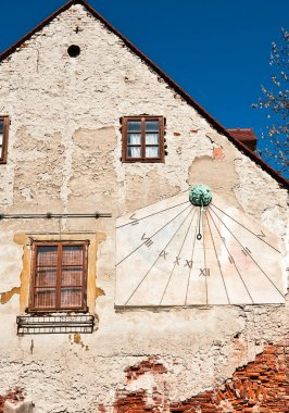 Sundial clock on old house wall.