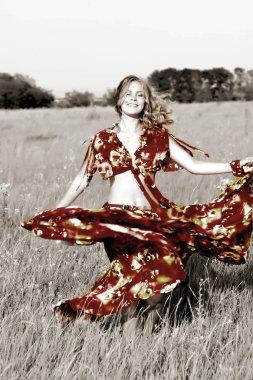 Beautiful girl in a bright dress dancing in a field