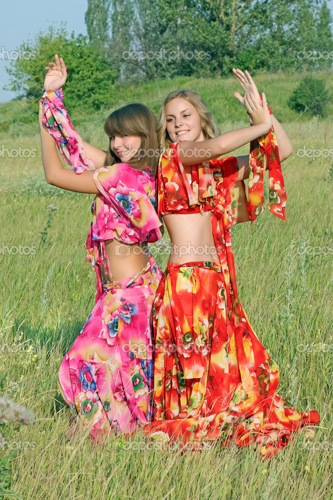Two young girls dancing in a field