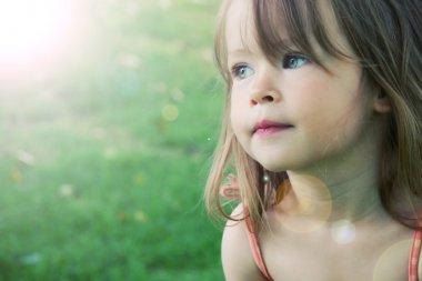 Adorable little girl taken closeup outdoors in s