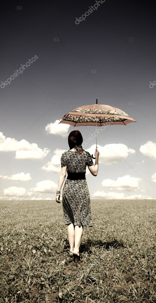 Girl with umbrella at green grass field in sunny day.