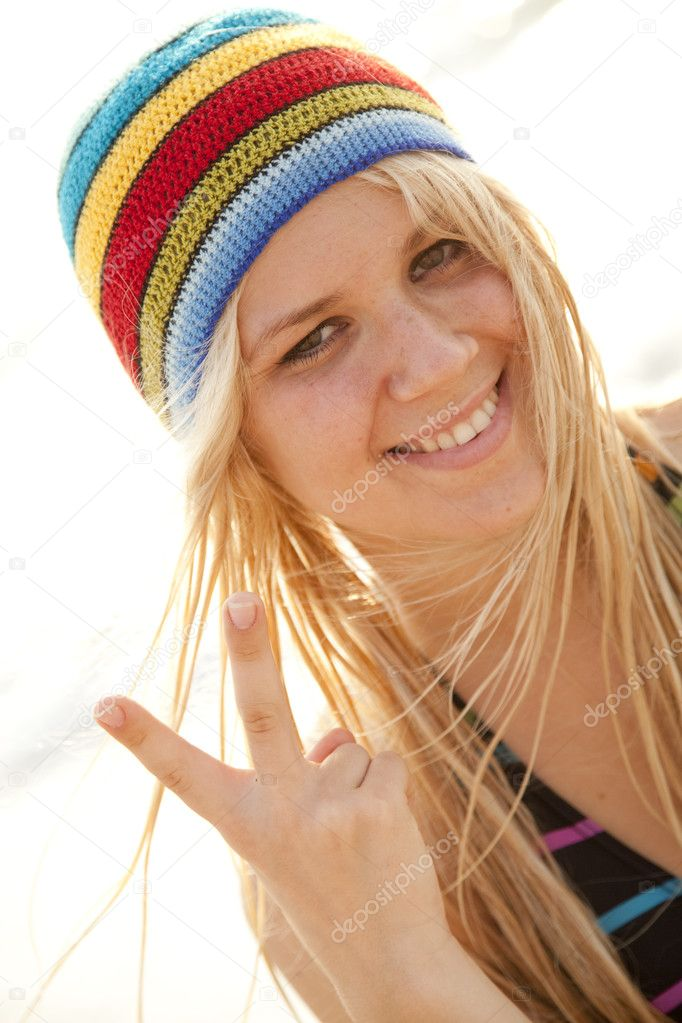 Beautiful young blonde girl in rastafarian hat show two fingers in V  symbol. Sunlight is on background. — Photo by massonforstock d5e2be66caf5