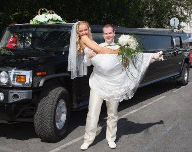 Wedding couple near limousine