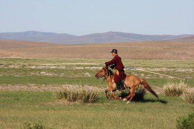 Mongolian horse herdsmen on horseback