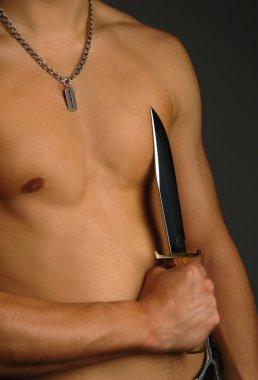Man holding knife on a torso