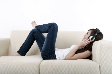 Beautiful young asian listening to music on a sofa
