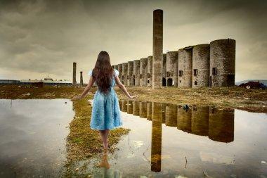 Woman walking among ruins