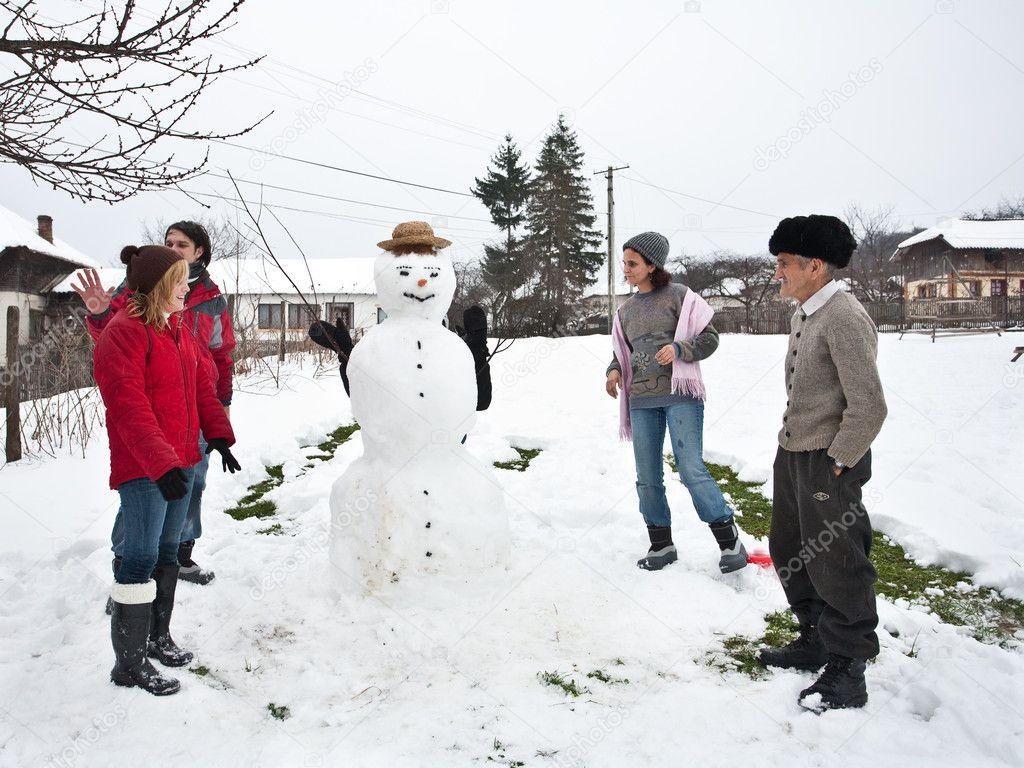 Happy family around a snowman