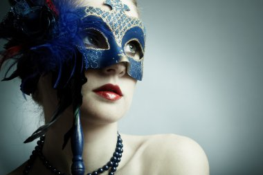 The beautiful young girl in a mask