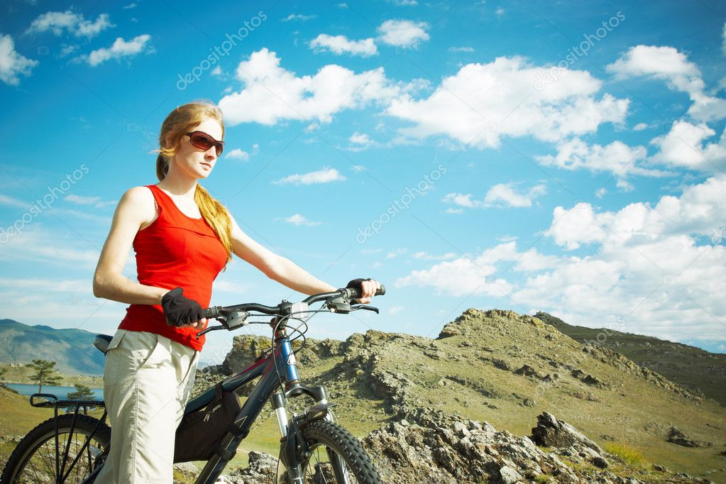 The girl with a bicycle against mountains
