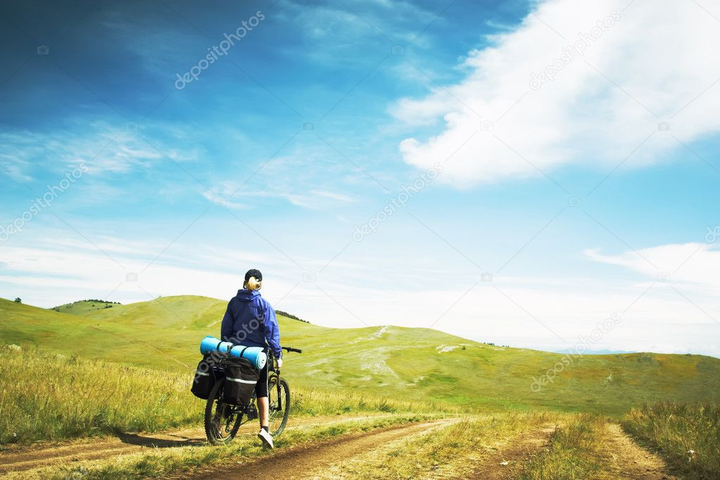 The woman going on a bicycle against mountains