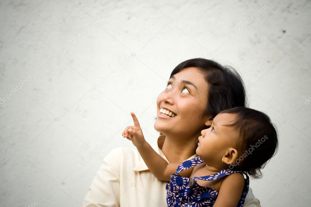 Asian mother and baby looking up and pointing