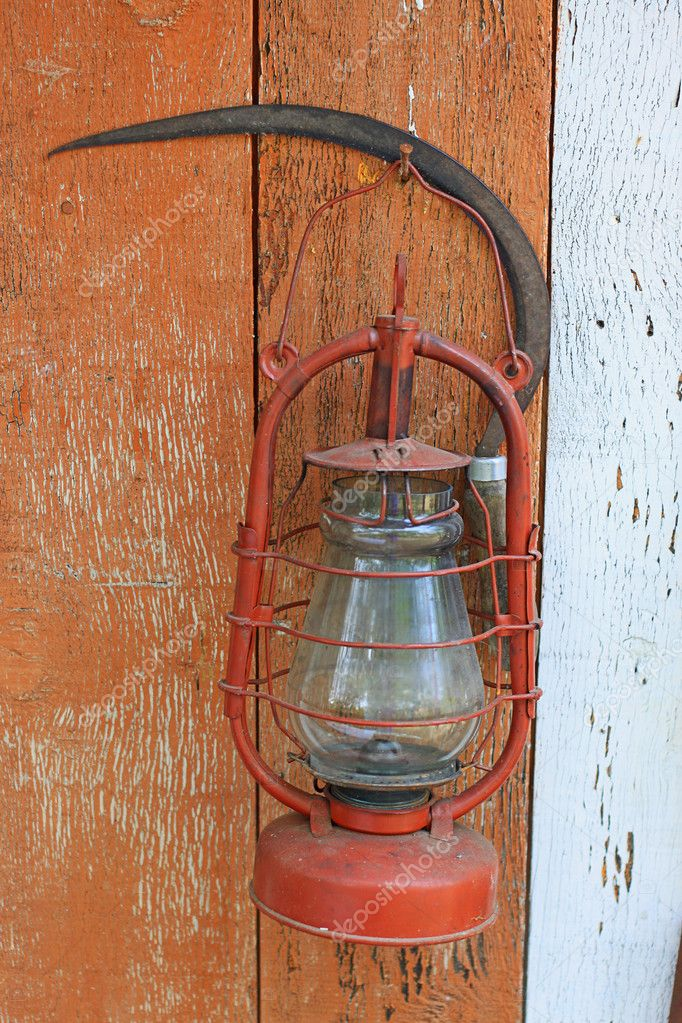 Age-old kerosene lamp and sickle on a peeling off wooden background