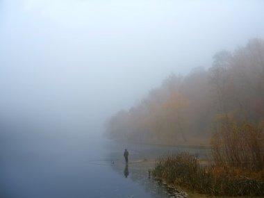 A fisherman on a misty lake