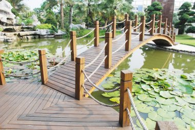 The wood board bridge in a water pond garden in a tropical resort China.
