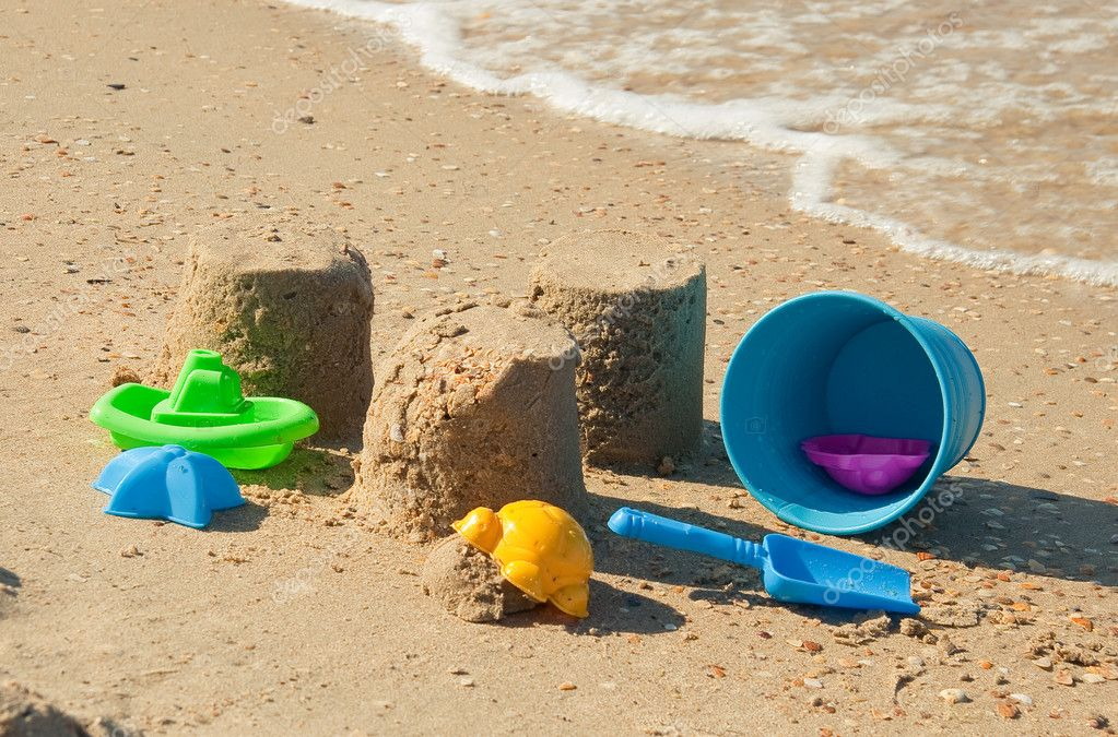 Colorful plastic toys on the sandy beach