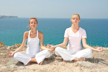 Two woman meditating in mountains
