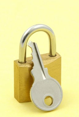 Close-up of padlock and key against yellow background stock vector