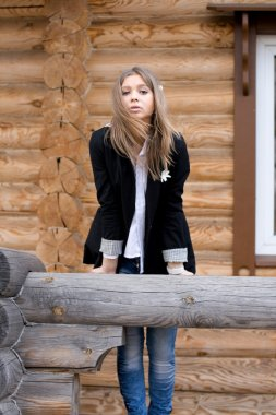 Girl in front of a wooden house
