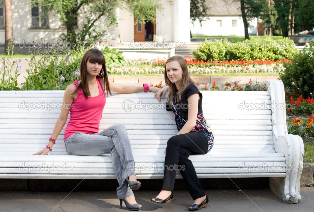 Two female friends sitting on bench