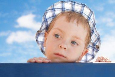 Sad cute little boy in hat on sky background