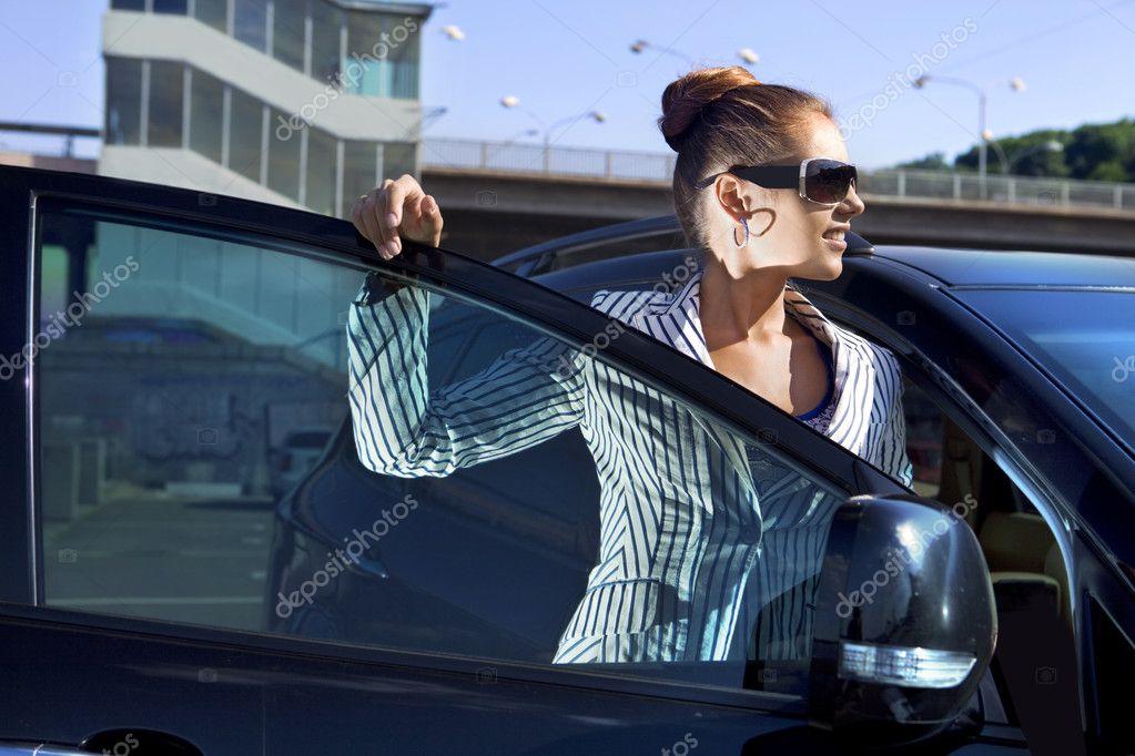 Бізнес жінка в сонцезахисні окуляри біля автомобіля проти місто міст — Фото  від ssuaphoto da1c8363665e7