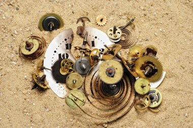 Parts of clockwork mechanism on the sand