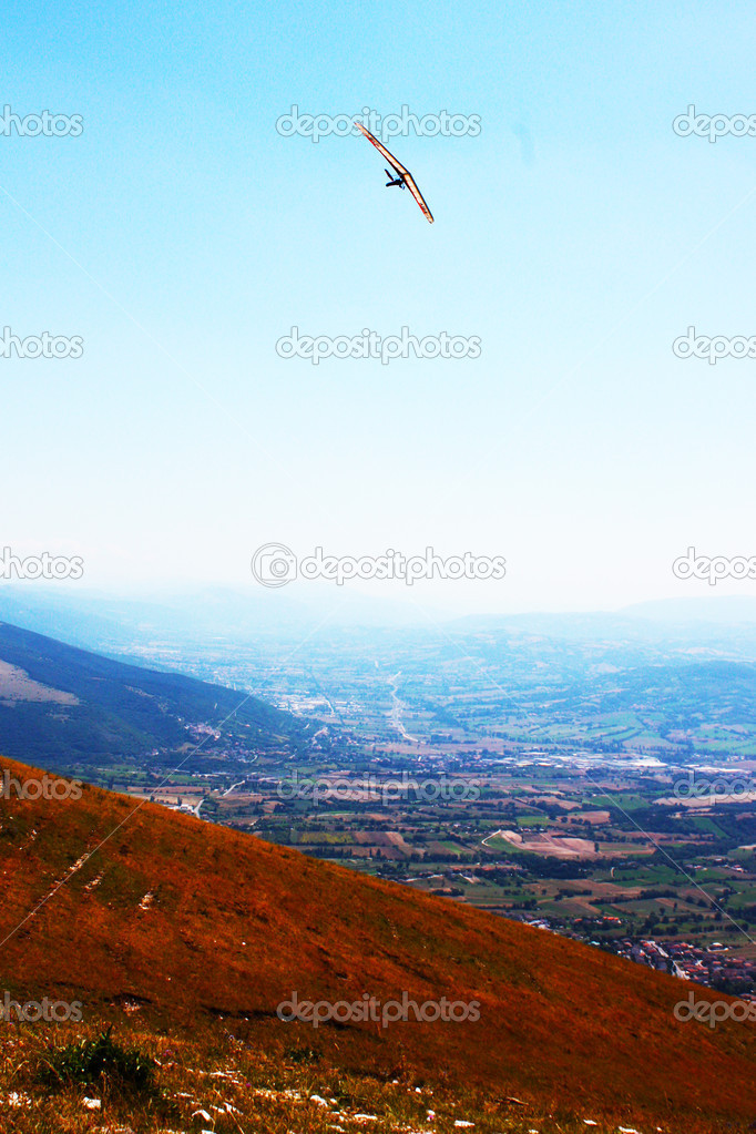 Hang glider flying in the mountains