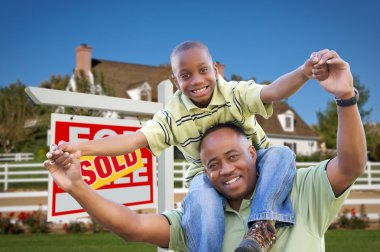 Father and Son in Front of Sold Sign