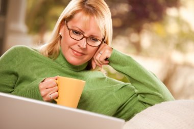 Smiling Woman with Cup Using Laptop