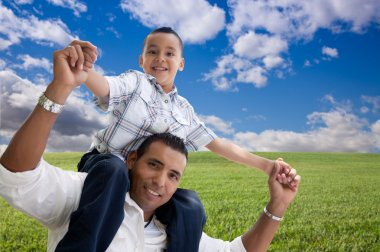 Happy Hispanic Father and Son Over Grass