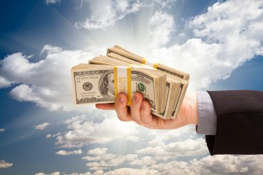 Male Hand Holding Stack of Cash Over Clouds and Sky