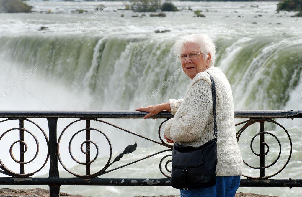 Senior woman sitting at edge of niagara