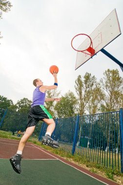 Young men playing street basketball at court playground