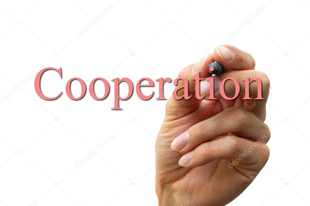 Hand writing the word cooperation