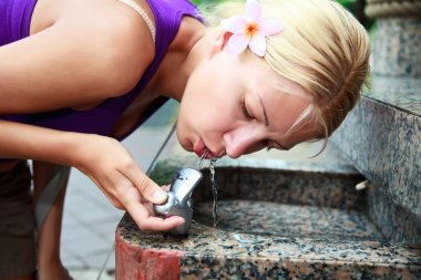 Girl drinking water from fountain