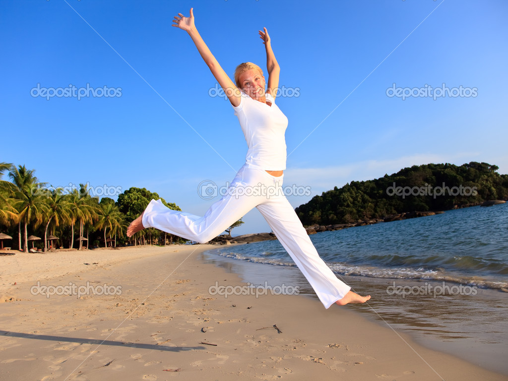Happy woman is jumping in the beach