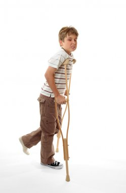 Wincing injured boy using crutches