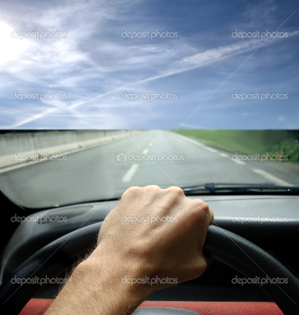 Detail of a man's hand holding the steering wheel of a car and driving on a highway