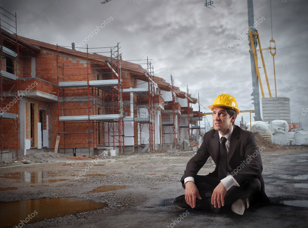 Engineer sitting in a construction site with cloudy sky on the background