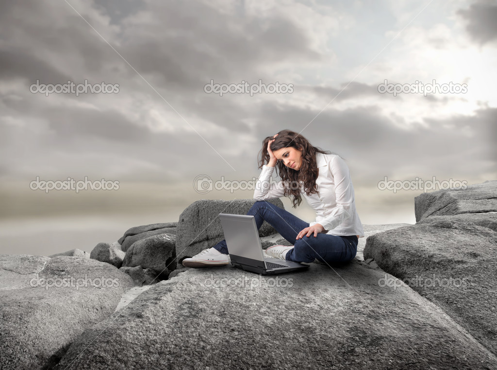 Young woman sitting on a stone and using a laptop