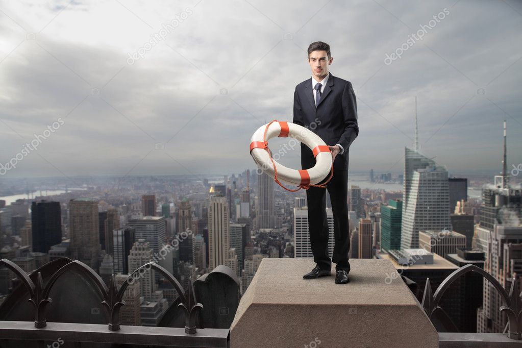Businessman holding a lifebelt in the rooftop of a skyscraper