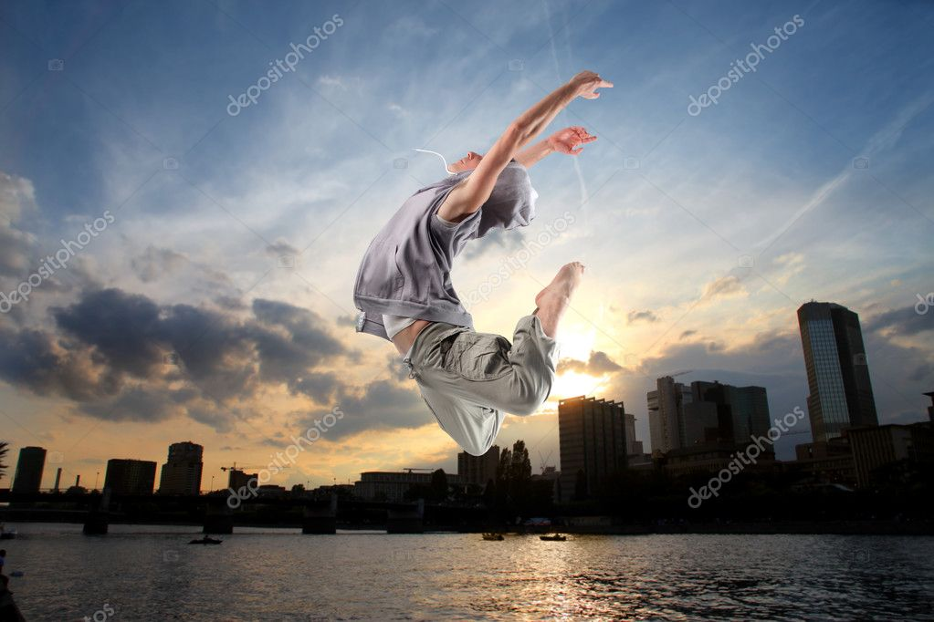 Young man dancing with cityscape on the background