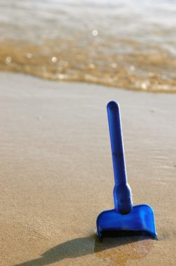 Child's toy spade on a beach
