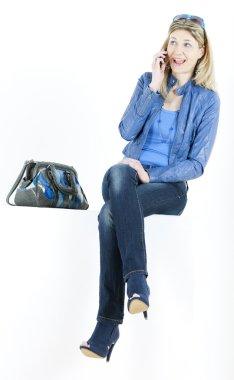 Sitting woman with mobile phone and handbag
