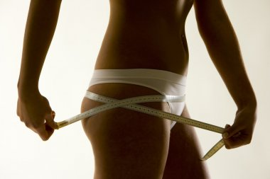 Detail of woman wearing underwear with tape measure