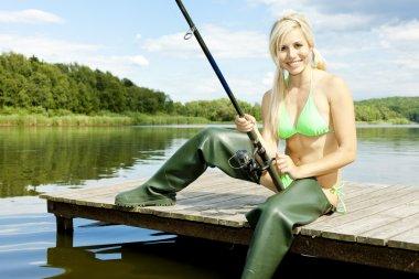 Fishing woman sitting on pier