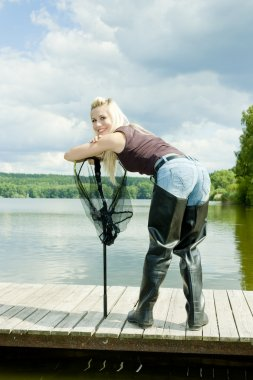 Fishing woman with landing net standing on pier