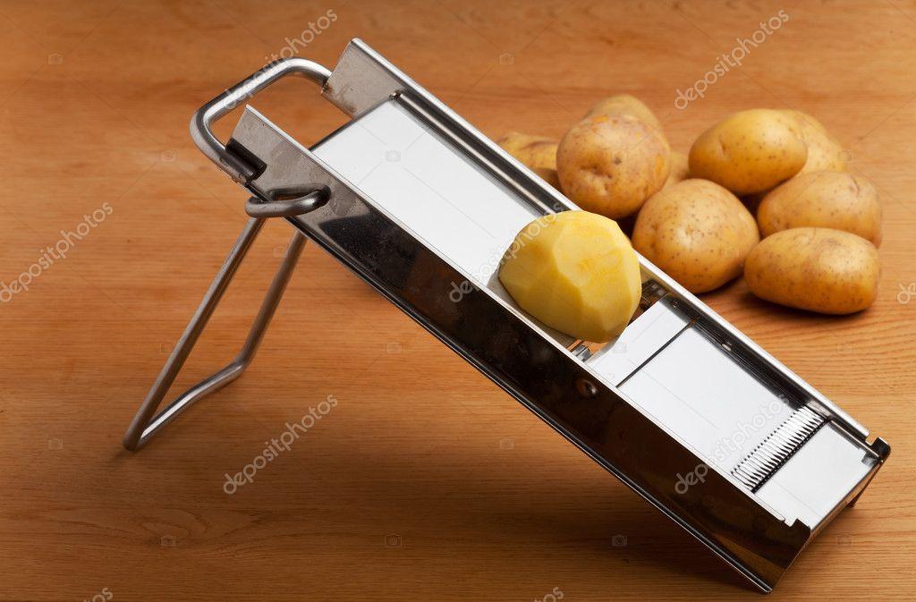 Half A Potato On A Mandolin Slicer Stock Photo