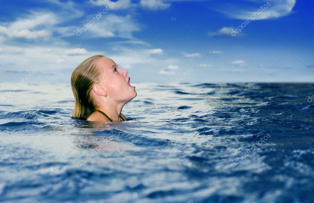 Cute preteen in the ocean looking up